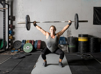 Front view of strong young woman lifting weights over her head
