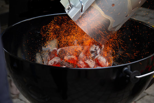Adding glowing charcoal to the grill
