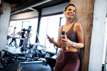 Young smiling woman at the gym relaxing and listening to music using a mobile phone Fototapete