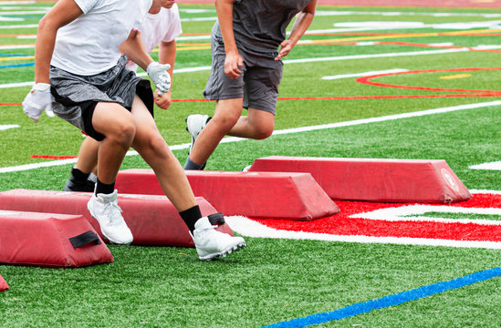 Football players at summer camp running between red barriers