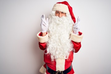 Middle age handsome man wearing Santa costume standing over isolated white background gesturing finger crossed smiling with hope and eyes closed. Luck and superstitious concept.