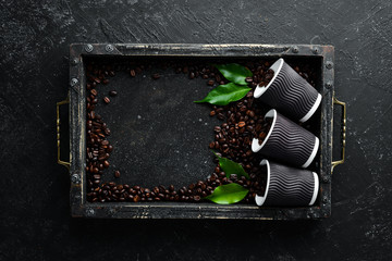 Paper cups for coffee and coffee beans. On a black stone background. Top view. Free space for your text.