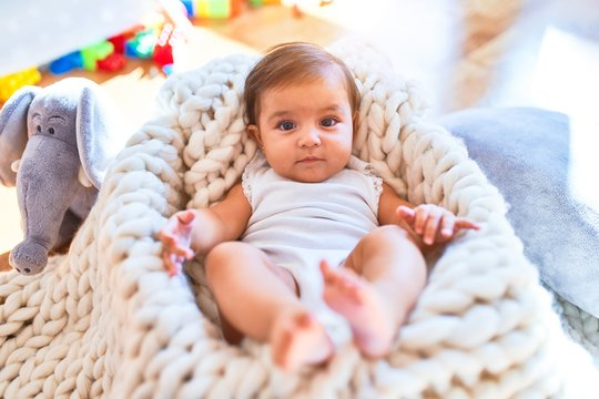 Beautiful infant happy at kindergarten around colorful toys lying inside crib