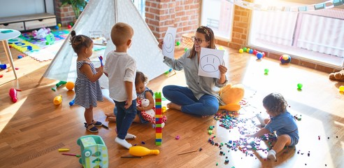 Beautiful psychologist and group of toddlers make therapy using emotions emojis around lots of toys at kindergarten