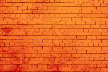 Brick wall painted in orange color splashed with red paint.