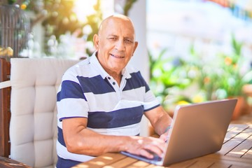 Senior handsome man smiling happy and confident. Sitting using laptop at terrace