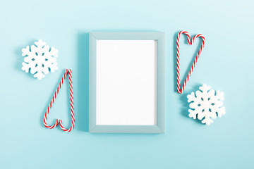 Christmas holiday composition. Photo frame, Xmas white and red decorations on pastel blue background. Christmas, New Year, winter concept. Flat lay, top view, copy space