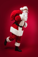 Hurry up! A full-length photo of Santa Claus, hurrying and running with a bag full of presents on his right shoulder and his left hand forming a fist.