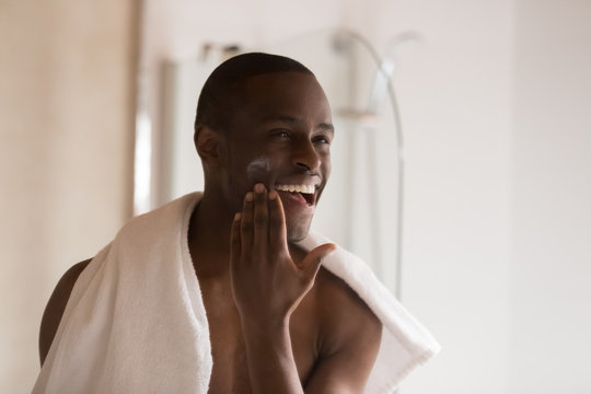Happy smiling african ethnicity man applying moisturizing balm on cheek.