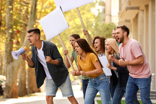 Angry young man with megaphone leading protest outdoors
