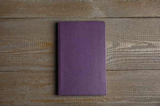 Hardcover book on wooden table, top view. Space for text