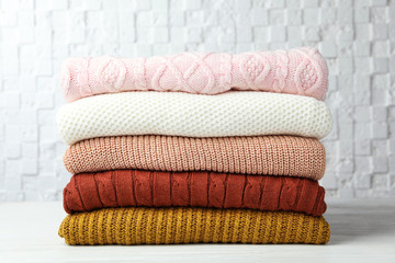Fototapete - Stack of warm clothes on white wooden table against textured wall. Autumn season