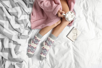Fototapete - Woman with cocoa wearing knitted socks on white fabric, top view. warm clothes