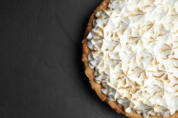 Delicious lemon meringue pie on black table, top view. Space for text