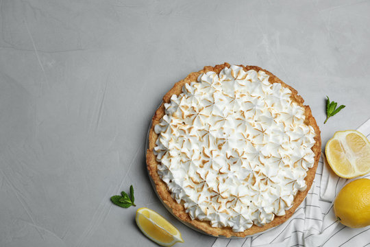 Flat lay composition with delicious lemon meringue pie on grey table