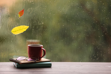 Composition with cup of drink and autumn leaf on windowsill, space for text. Rainy weather