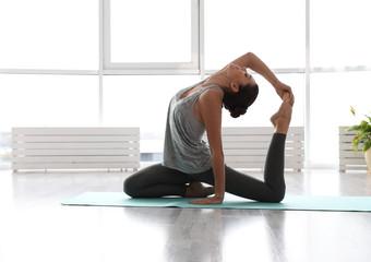 Young woman practicing one legged king pigeon asana in yoga studio. Eka Pada Rajakapotasana pose