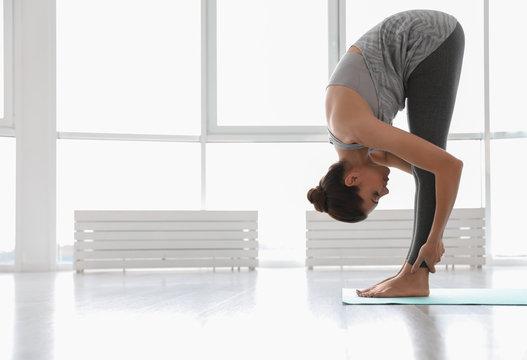 Young woman practicing standing forward bend asana in yoga studio. Uttanasana pose