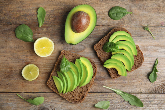 Flat lay composition with avocado toasts on wooden table