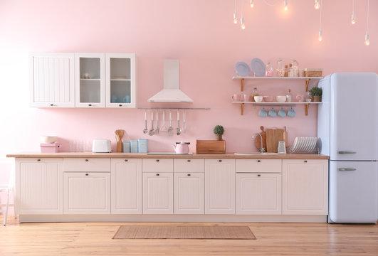 Stylish pink kitchen interior with modern furniture and fridge