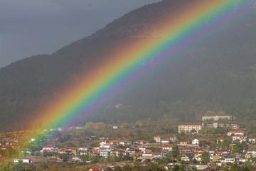 Regenbogen über einem kleinen Ort im Gebirge