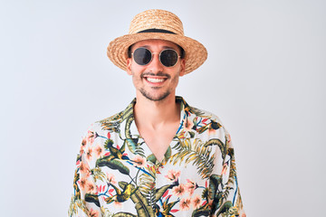 Young handsome man wearing Hawaiian shirt and summer hat over isolated background with a happy and cool smile on face. Lucky person.