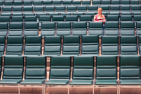 A small part of the auditorium with several rows of chairs in blue-green. There is only one viewer in the photo. A woman is sitting in the upper right corner of the frame. Background