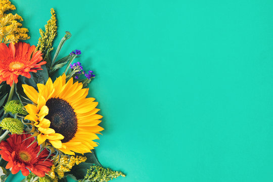 Corner border of different fresh bright colorful summer flowers lying on trendy mint background. Flat lay style. Copy space.