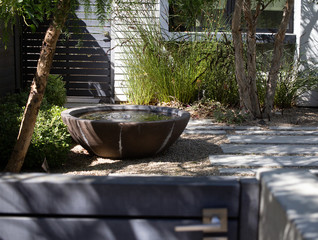 modern water fountain in garden with bamboo reeds