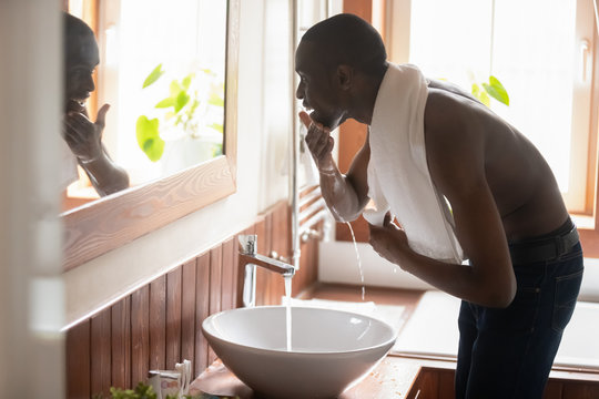 Smiling african american guy bending over sink with running water.