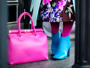 Woman in autumn or spring in a bright coat and a pink big bag. Blue boots, boots. Fashionable bag close-up in female hands.Girl walks in the city outdoors. Stylish modern and feminine image, style.