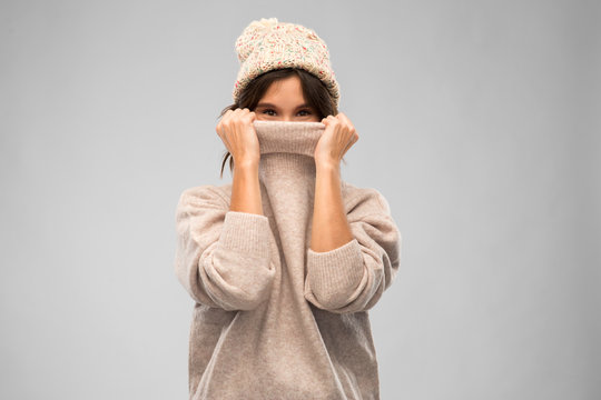 winter season and people concept - happy young woman in knitted hat covering face with warm sweater over grey background
