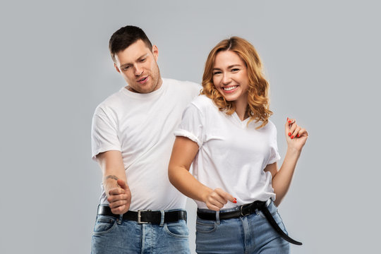 relationships and people concept - portrait of happy couple in white t-shirts dancing over grey background