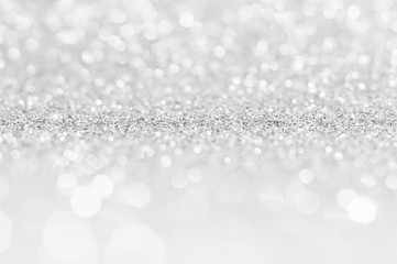 Silver white abstract light grey background, shining lights, sparkling glittering Christmas lights. Blurred abstract holiday background.