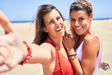 Young beautiful friends on vacation wearing swimsuit smiling happy and confident. Standing with a smile on face make selfie by camera at the beach