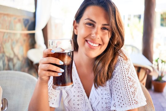 Young beautiful woman sitting at restaurant enjoying summer vacation drinking soda