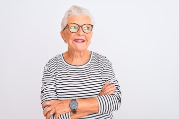 Senior grey-haired woman wearing striped navy t-shirt glasses over isolated white background smiling looking to the side and staring away thinking.