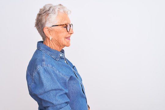 Senior grey-haired woman wearing denim shirt and glasses over isolated white background looking to side, relax profile pose with natural face and confident smile.