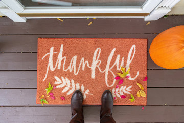 "Welcome mat with the word ""Thankful"" on front doorstep"