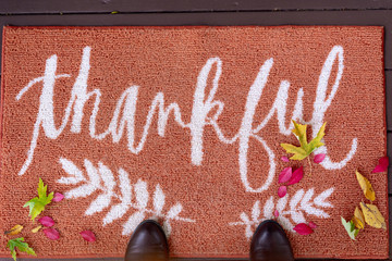 """Looking down at a welcome mat with the word """"Thankful"""""""