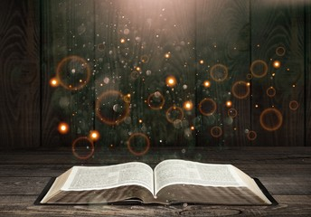 Wall Mural - Open book on old wooden table.