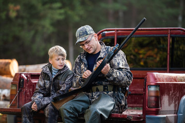 Poster de jardin Chasse Father and son sitting in a pickup truck after hunting in forest. Dad showing boy mechanism of a shotgun rifle.