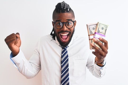 African american businessman with braids holding dollars over isolated white background screaming proud and celebrating victory and success very excited, cheering emotion