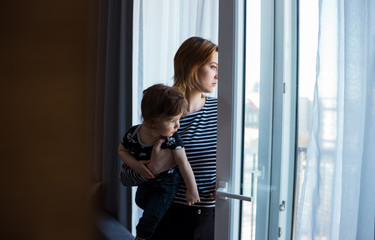 Young mother waiting by the window for her husband. Natural light, soft, out of focus image.