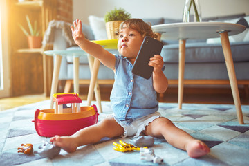 Beautiful toddler child girl sitting on the carpet playing with smartphone