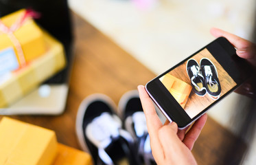 young woman taking photo sneakers with camera smartphone for post to sell online on the internet market website / selling online ecommerce shipping online shopping delivery and order