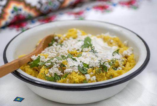 Traditional Eastern European corn mush (mamaliga, polenta, banosh, balmes) topped with sheep cheese and cream, served in an enameled bowl