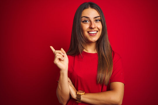 Young beautiful woman wearing t-shirt standing over isolated red background with a big smile on face, pointing with hand and finger to the side looking at the camera.