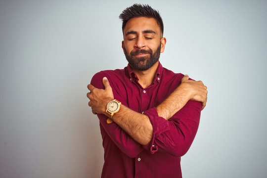 Young indian man wearing red elegant shirt standing over isolated grey background Hugging oneself happy and positive, smiling confident. Self love and self care