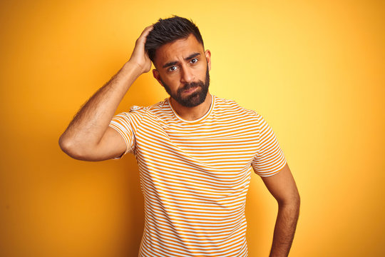 Young indian man wearing t-shirt standing over isolated yellow background worried and stressed about a problem with hand on forehead, nervous and anxious for crisis